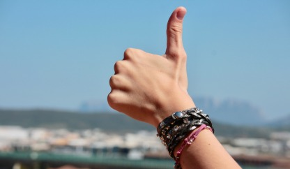 hand with bracelets giving a thumbs up